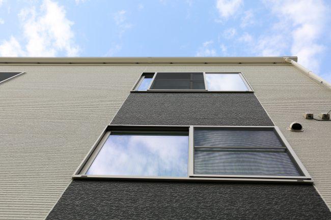 3階建ての外壁とサッシを下から見上げる