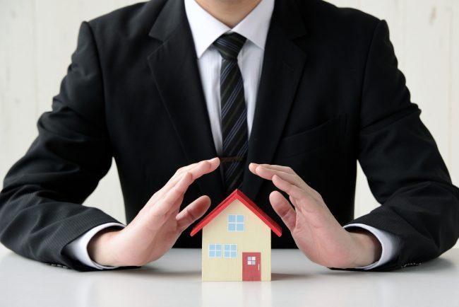 住宅を守るビジネスマン 地震保険のイメージ