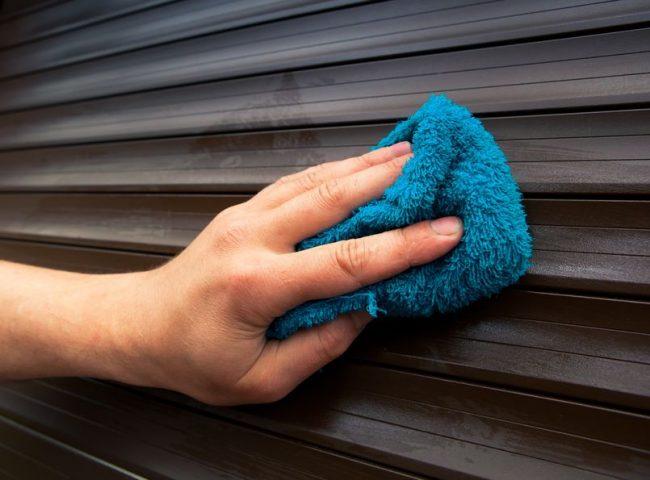 外壁を青いタオルで掃除している写真